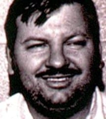 John Wayne Gacy smiling for mug shot.