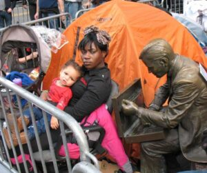A bronze statue of a Wall Street trader leans toward a jobless mother and her child at Occupy Wall Street.