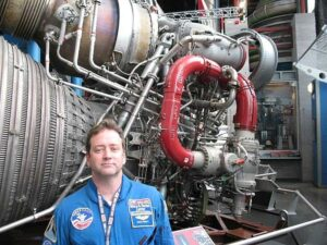 Tour guide stands before an F-1 rocket engine