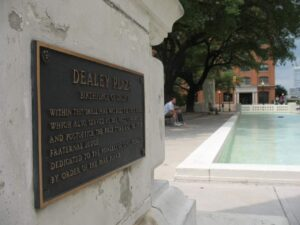 Dealey Plaza reflecting pool and Texas School Book Depository in background.