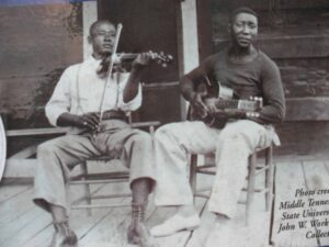 Young Muddy Waters playing guitar at his cabin