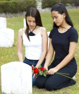 Two girls mourning the victim of a mass shooting in Colorado