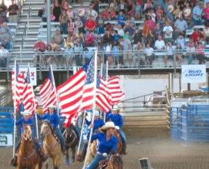 Cowgirls carry flags at the rodeo in Cody, Wyoming