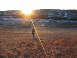 Sioux man walks toward the sunset on the Pine Ridge Indian Reservation