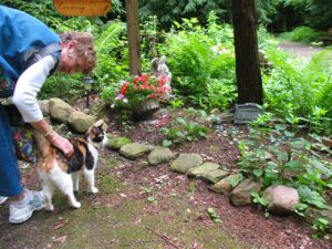 Adele Bowen pets a cat at the pet cemetery in Lily Dale