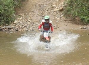 Randy Gray blasts through a creek on his dirt bike at Carolina Adventure World