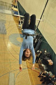Joan Anundsen hangs from the trapeze
