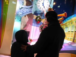 A father shares a tender moment with his son before Macy's Christmas windows in Chicago