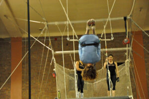 Joan Anudnsen with legs hooked over the trapeze