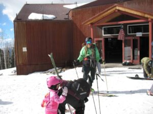 Jaimé Palmer greets a mother and child at the top of the gondola at Telluride
