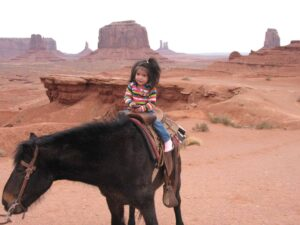Navajo child riding a horse at Monument Valley