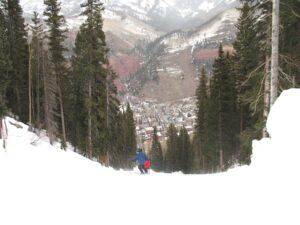 Skiers headed down Lower Plunge, the town of Telluride below.