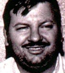 John Wayne Gacy smiling for mug shot.