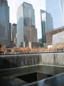 The 9/11 Memorial with the new World Trade Center rising behind it.