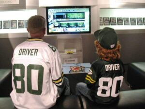 Father and son Packer fans play Madden 2011 at the Pro Football Hall of Fame.