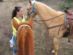 Mary with horses at the Running R Ranch in Bandera, TX