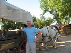 Malcolm Logan standing beside a covered wagon at The Oregon Trail Wagon Ride