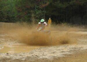Randy Gray smashes through a mud bog sending up a curtain of spray