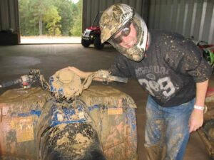 Malcolm Logan with his ATV covered in mud at Carolina Adventure World