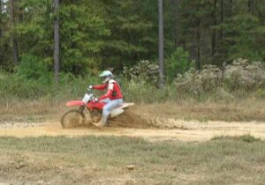 Randy Gray grinding through the mud on a rented dirt bike at Carolina Adventure World