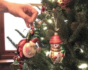 Marianne Grisdale hanging Christmas ornaments on the tree