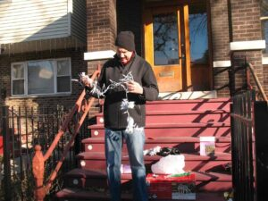 Malcolm Logan struggles with Christmas lights on the steps of his home in Chicago