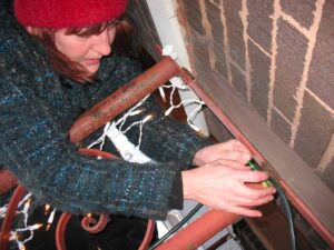 Marianne Grisdale putting up Christmas lights outside her home in Chicago
