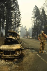 National guardsman by burnt out car
