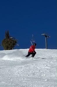 A skier turns on a slope beneath Seattle Ridge