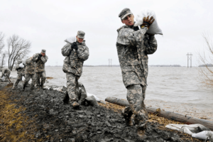 Carrying sandbags atop the levee