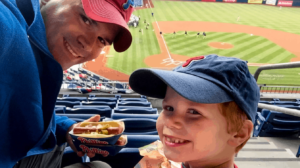A boy with his father at a baseball game.