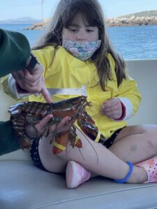 A child gets acquainted with a lobster on board the Lulu lobster boat