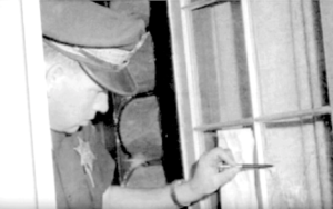 Police officer inspecting the bullet hole